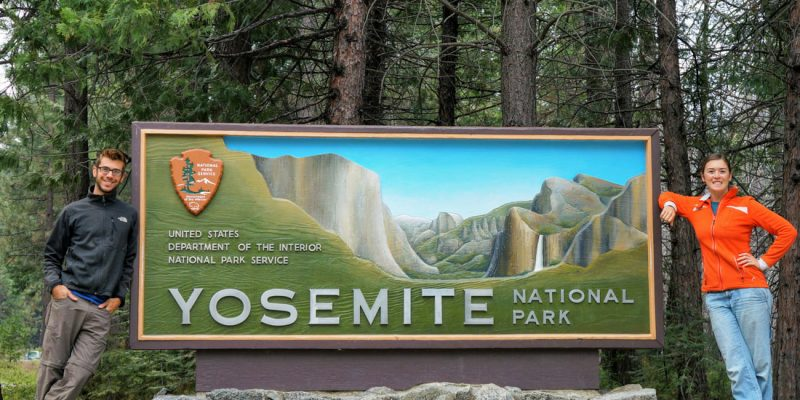 tom morton and cait morton standing at the yosemite national park sign
