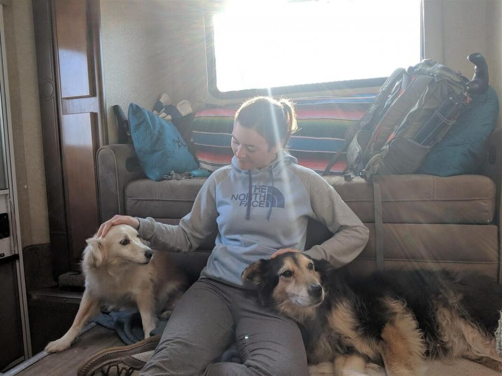 Cait on floor of truck camper with dogs